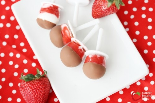 bright red and white swirled popsicles dipped in chocolate on a white plate, with polka dot placemat underneath