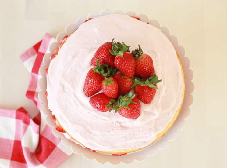 overhead view of a vanilla cake with whole strawberries on top