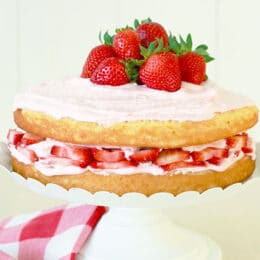 Vertical image of low sugar vanilla cake with homemade strawberry frosting
