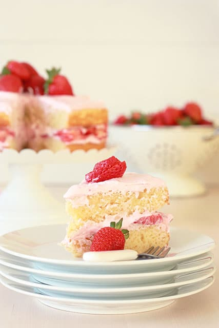 A slice of vanilla cake with strawberry frosting and strawberries on a plate