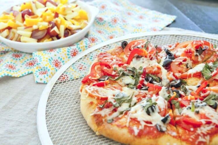 grilled pizza on an outdoor table next to fruit salad