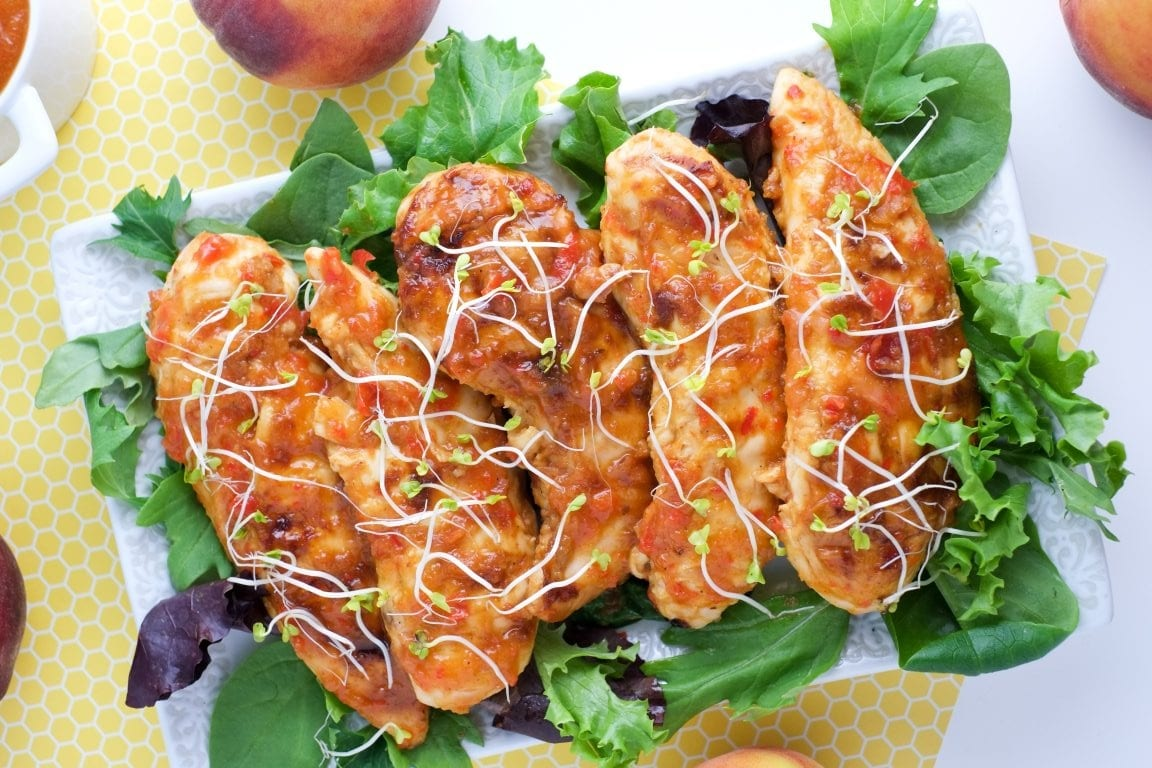 grilled peach chicken tenders on a bed of lettuce