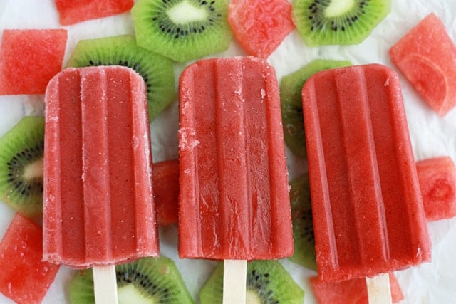 red popsicles surrounded by fresh watermelon and kiwi slices
