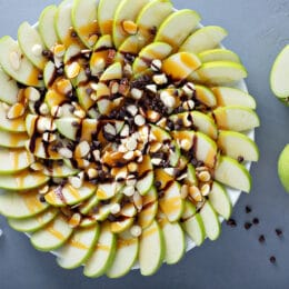 Apple nachos with white and dark chocolate chips, caramel syrup and almonds