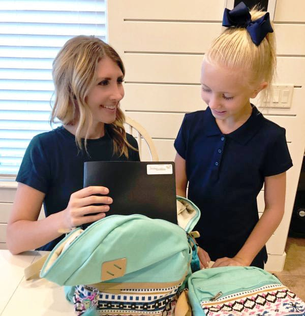 mom and daughter packing a backpack