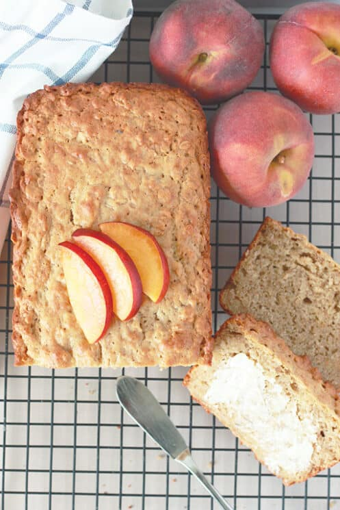 Sliced peach crisp bread with 3 peaches in the background