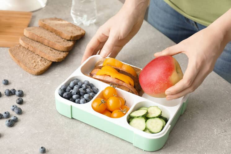 packing food into a bento style lunch box
