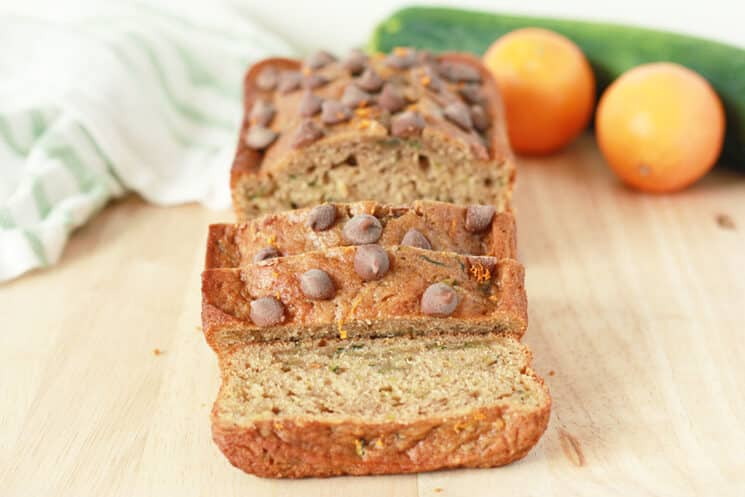 Orange zucchini bread loaf with chocolate chips on top, with slices.