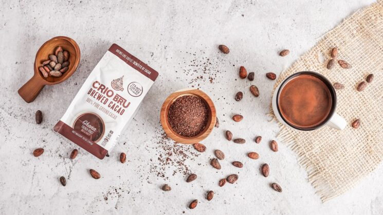 Crio Bru package with cacao beans spread around it and ground cacao in a bowl