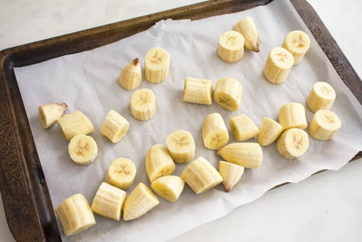 frozen banana pieces on a tray with parchment paper