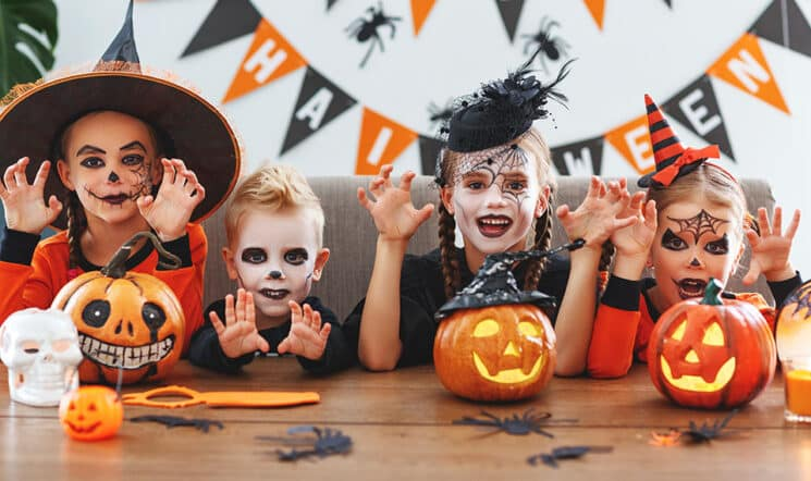 a group of children in halloween costumes with pumpkins in the home