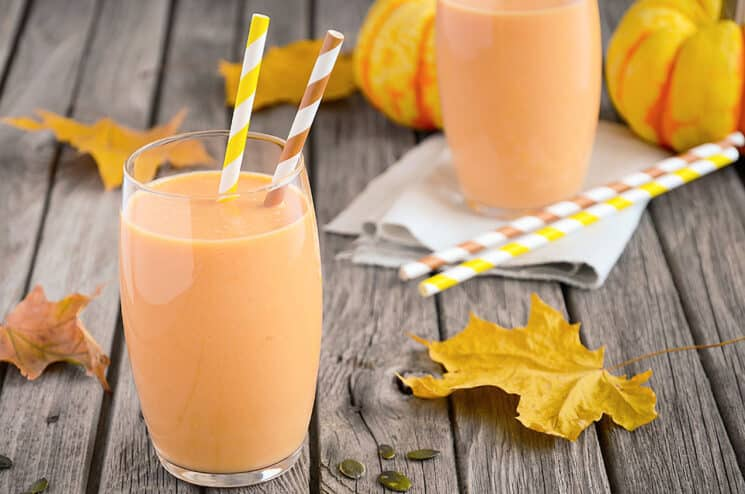 pumpkin smoothie with festive straws and fall leaves in the background