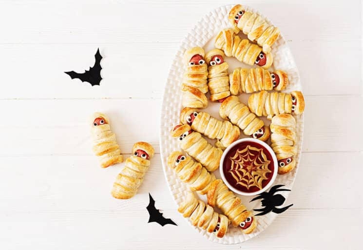 mummy hot dogs on a white plate with a ketchup mustard spider webb sauce on the plate. paper bats as decorations on the table.