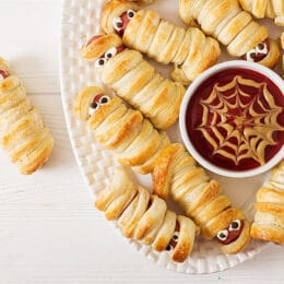 mummy hot dogs top view with spider web mustard and ketchup dip