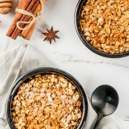 pumpkin pie oatmeal in two bowls with cinnamon sticks in the background