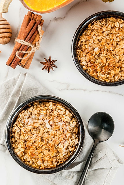 two bowls of pumpkin oatmeal with cinnamon sticks in the background