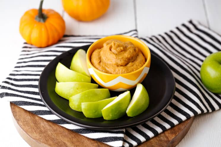 pumpkin spice dip with green apples surrounding the bowl of dip