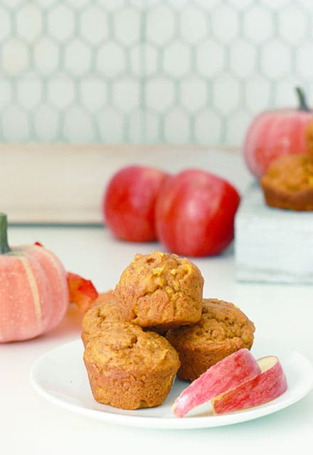 4 pumpkin and apple muffins on a plate with sliced ​​apples next to them and apples in the background
