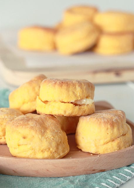 sweet potato biscuits on a wooden plate stacked with sweet potato biscuits in background