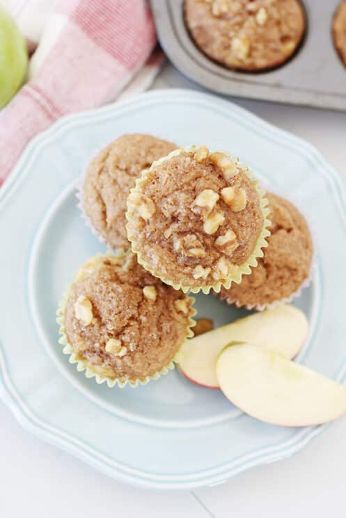overhead view of whole wheat applesauce muffins on a plate with sliced apples