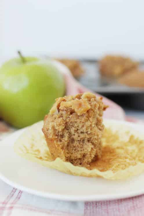 close up of a whole wheat applesauce muffin broken in half on a plate