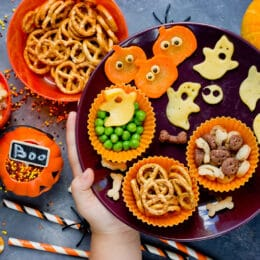 halloween snack mix on a plate with childs hands setting it down