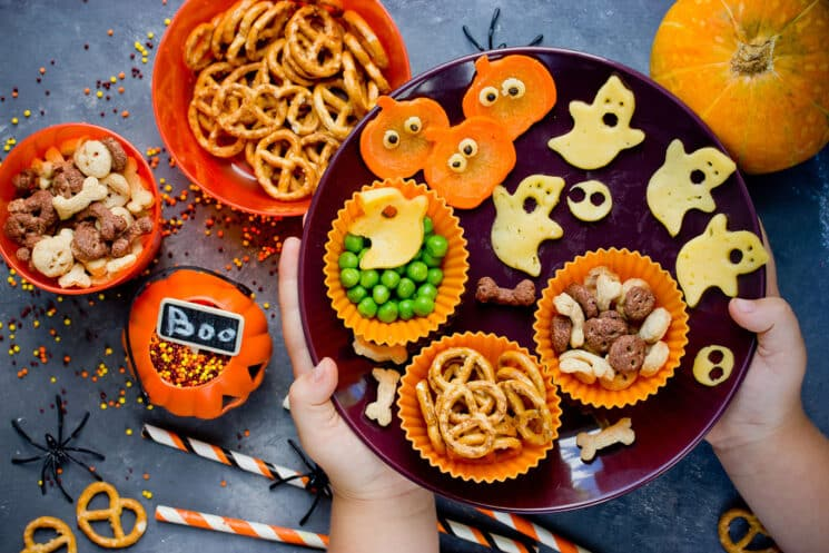 halloween snacks with a childs hands setting down the plate full of snacks