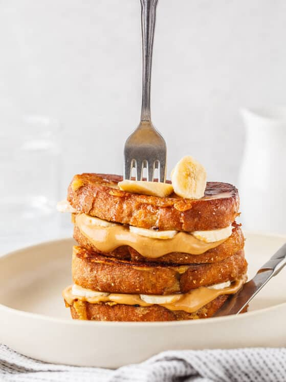 stack of peanut butter banana french toast with a fork vertically stuck in the stack