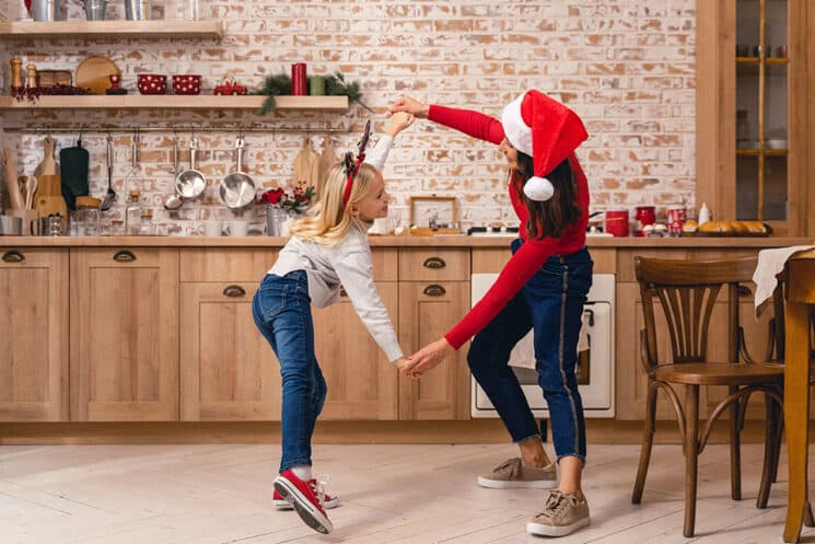 Happy child and her mother having a great time dancing in the kitchen on christmas eve