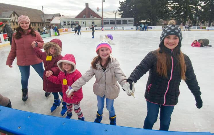 a family of girls holding hands while ice skating