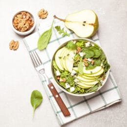 Autumn harvest salad with sliced ​​pears, spinach, feta cheese crumble and walnuts