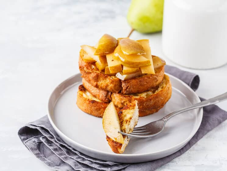 stack of warm pear french toast with a bite cut out on a fork and a pear in the background