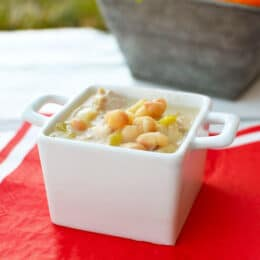 white bean chicken chili in a white small square dish with a red placement underneath