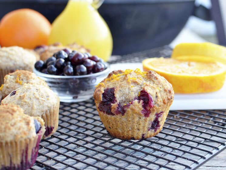 Whole wheat blueberry muffins on a refrigerated shelf with blueberries and oranges in the background