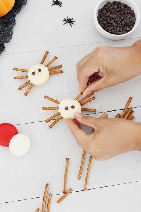 spider bites healthy halloween snack made of baby bell cheese and pretzel sticks for legs