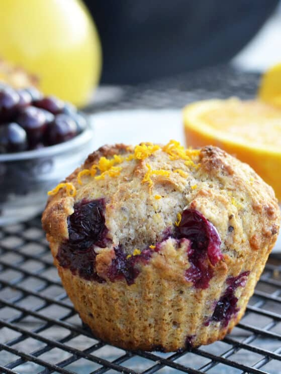 whole wheat orange blueberry muffin with blueberries and an orange in the background