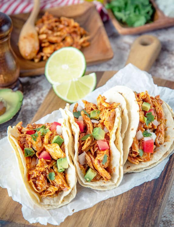 Crockpot Chicken Tacos with Chicken and Limes in the Background