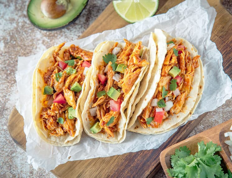 crockpot chicken tacos on a wood board with avocado, tomatoes and cilantro
