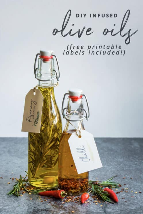 Clear glass bottles with oil, rosemary and chilis with paper tag