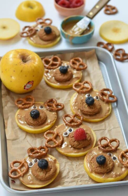 Apple slices topped with peanut butter, cookies and pretzels to resemble reindeer on a baking sheet