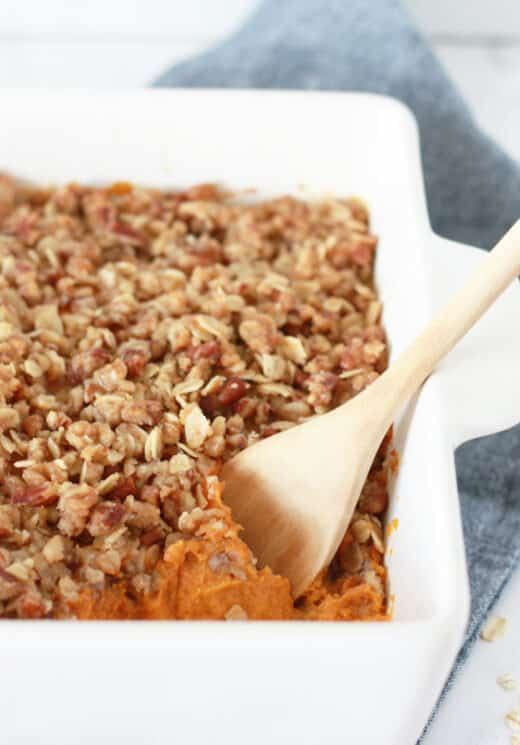 Sweet potato casserole with pecan oat crumble in a white baking dish with a wooden serving spoon