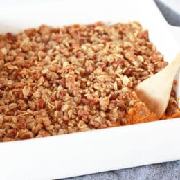 sweet potato casserole with a pecan oat crumble topping in a white baking dish with a wooden serving spoon
