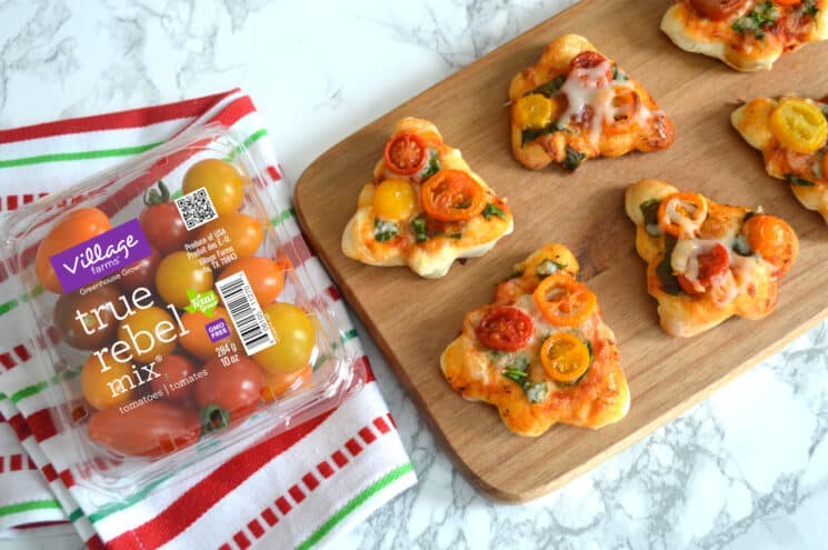 Mini pizzas in the shape of trees on a wooden cutting board