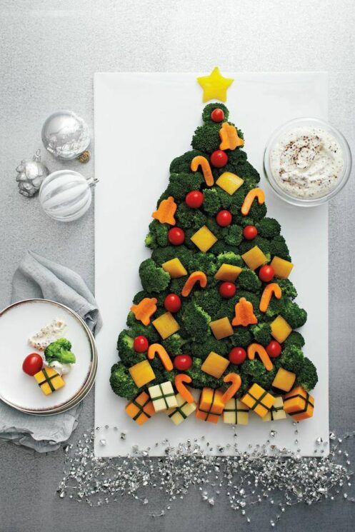 Broccoli tree topped with carrots cut into ornament shapes on a white platter