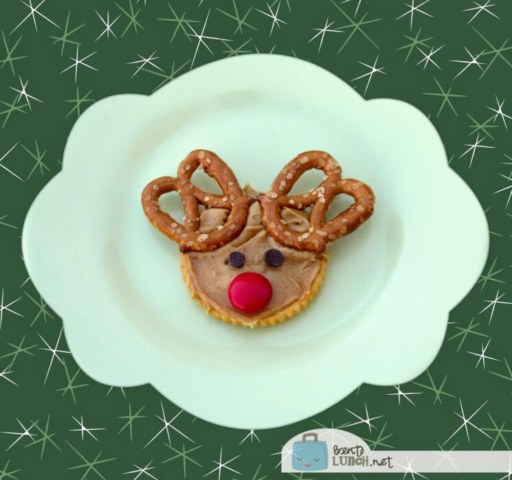 Crackers topped with peanut butter and antlers made of pretzels and a red candy nose