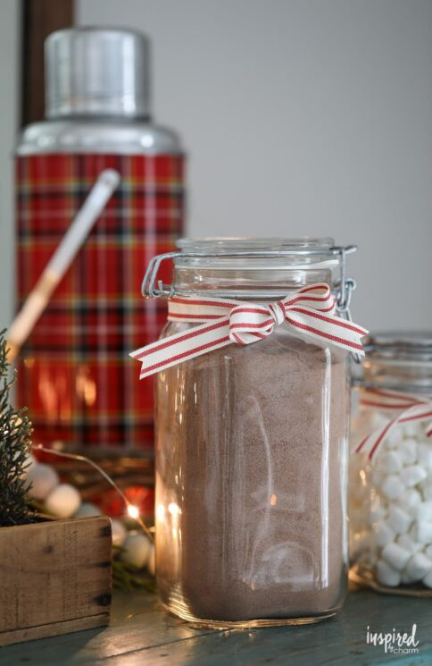 large glass jar with hot cocoa mix tied with a ribbon on a table with holiday decor