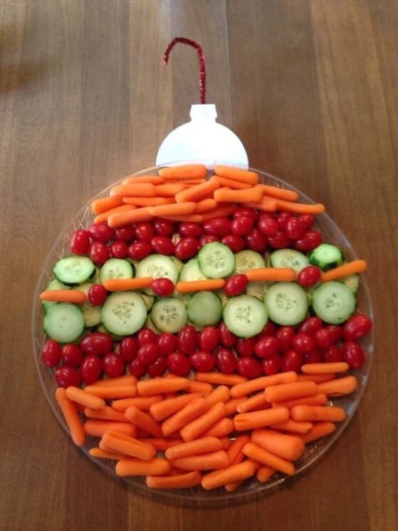 A round plate with carrots and tomatoes in stripes topped with a pipe cleaner to make an ornament
