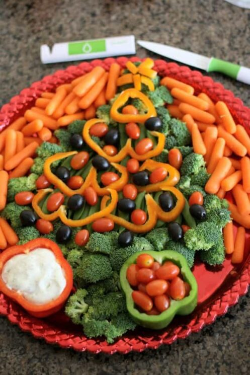 Christmas tree made with broccoli, bell peppers, olives and tomatoes with a bell pepper as a dip bowl on a red platter