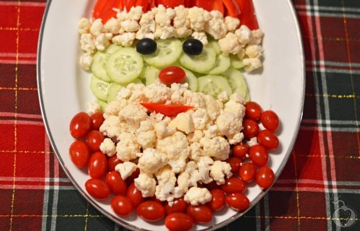 Santa face made with cauliflower, cherry tomatoes, and cucumber slices on a plaid background