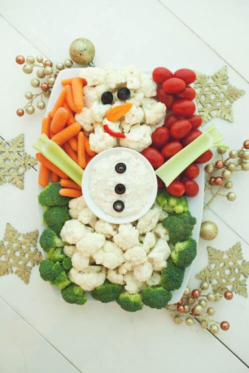 Cauliflower snowman surrounded by broccoli, carrots and tomatoes on a christmas background